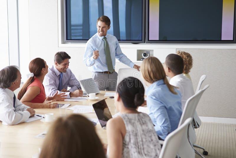 Motivational högtalare som talar till Businesspeople i styrelse royaltyfri fotografi
