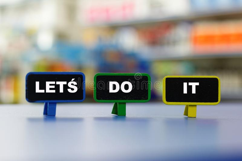 Motivational and inspirational words LET`S DO IT with colourful blurred background. stock photography