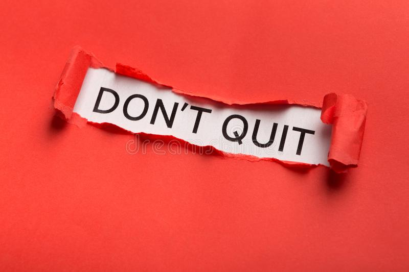 Dont quit phrase bursting out from torn red paper. Motivational poster with Dont quit phrase appearing behind torn red paper. Inspiration and support concept royalty free stock photo