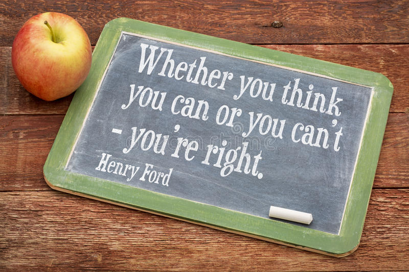 Motivational quote by Henry Ford. Whether you think you can or you can't - you're right, motivational quote by Henry Ford on a slate blackboard against red barn royalty free stock photography