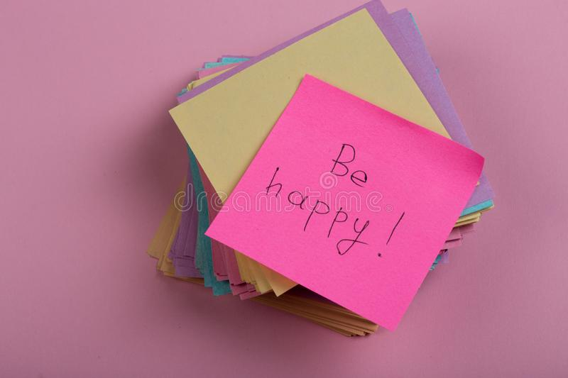 """Motivational slogan- Text on pink sticker """"be happy"""" on pink background stock photo"""