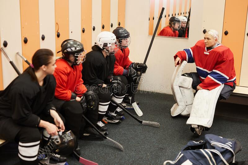 Motivational Speech Before Hockey Match. Portrait of female hockey team captain giving motivational pep talk in locker room before match, copy space stock photography