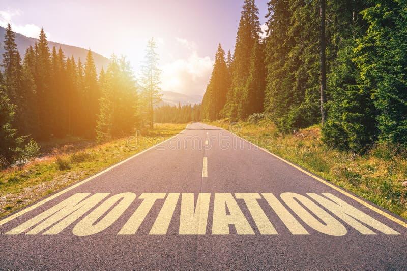 Motivationord som är skriftligt på vägen i bergen royaltyfri bild