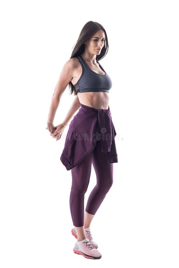 Motiverad ung färdig kvinna i sportig kläder som sträcker armmuskler som förbereder sig för idrottshallövning arkivbild