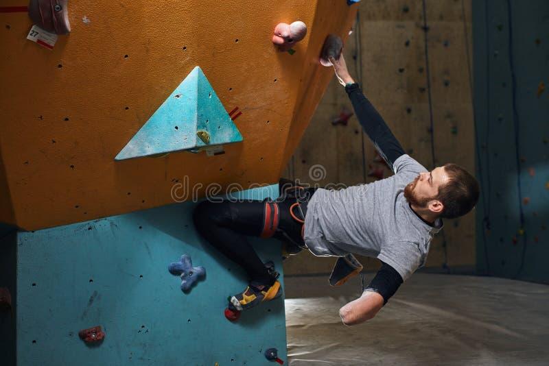 Motiverad vagga-klättrare med utbildning för fysiskt handikapp på konstgjorda klättraväggar royaltyfri fotografi