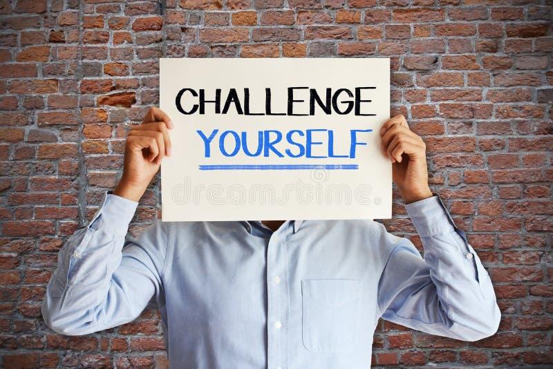 """Motivmitteilung """"challenge yourself† handgeschrieben auf weißem Blatt Papier in den Geschäftsmannhänden lizenzfreie stockfotografie"""