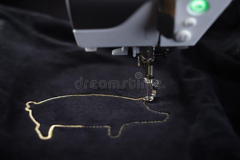 Motivo de costura del cerdo de la máquina del bordado con hilado del oro en tela del negro velvetely fotos de archivo