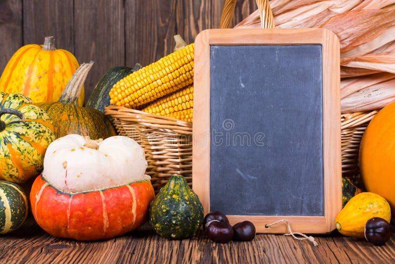 Motivo del raccolto di autunno con le varie zucche davanti ad un canestro con le pannocchie di granturco su un fondo di legno rus immagini stock