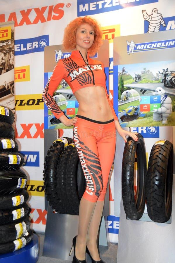 Moto公园2015年 在橙色衣服的印象深刻的模型在保护者一位立场已知的制造商运作 库存照片