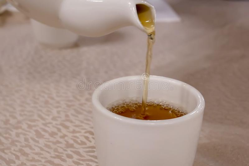 Moto della gente che versa tè caldo dentro il ristorante cinese immagine stock