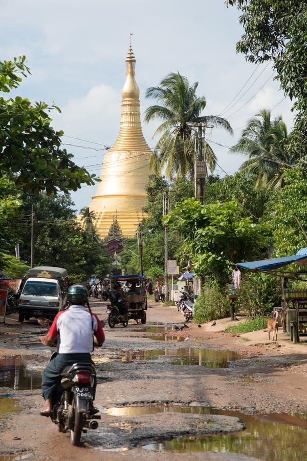 Moto et vue d'équitation d'homme sur la pagoda d'or dans le bago, myanmar image stock
