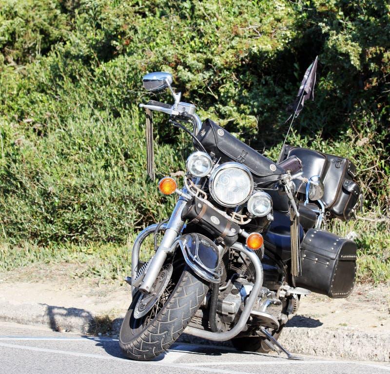 Moto faite sur commande de vintage noir se tenant sur la route dans une localité de mer photos stock