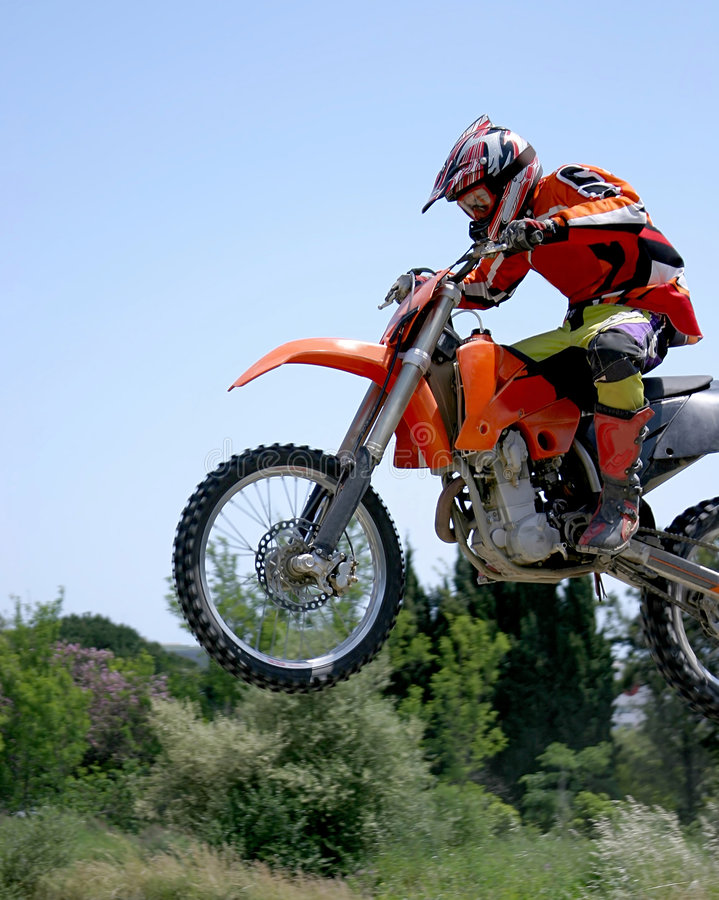 Moto X Motorbike jumping through the air on a hot sunny day with blue sky royalty free stock photo