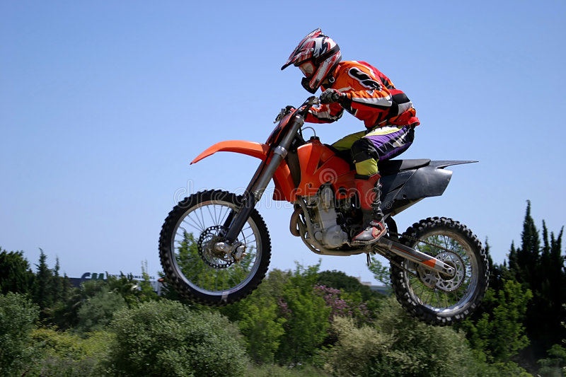 Moto X Motorbike jumping through the air on a hot sunny day with blue sky royalty free stock image