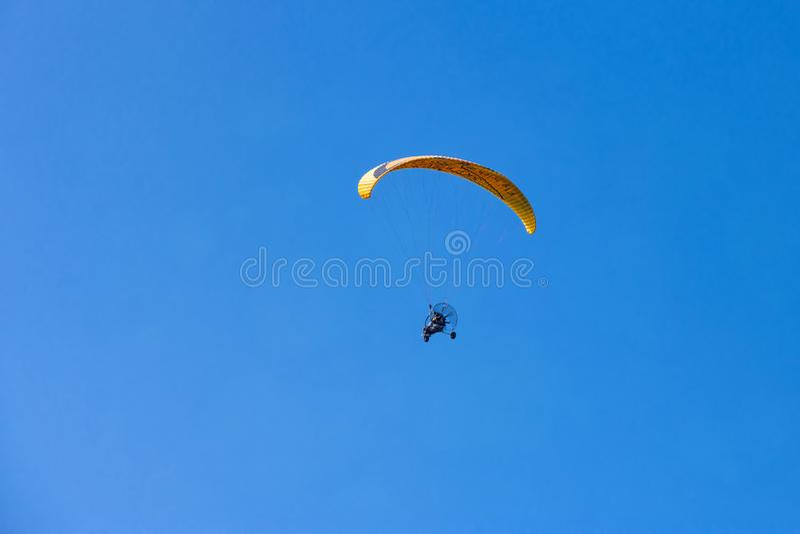 Moto-paraglider amarelo que voa sobre o céu azul claro imagem de stock
