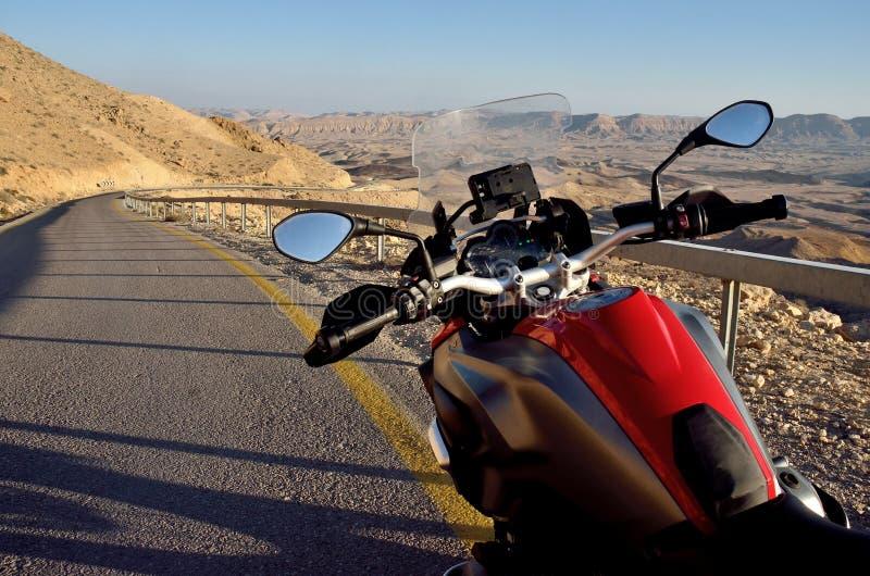 Moto roja en el camino en desierto del Néguev cerca del cráter grande, Israel, Medio Oriente foto de archivo