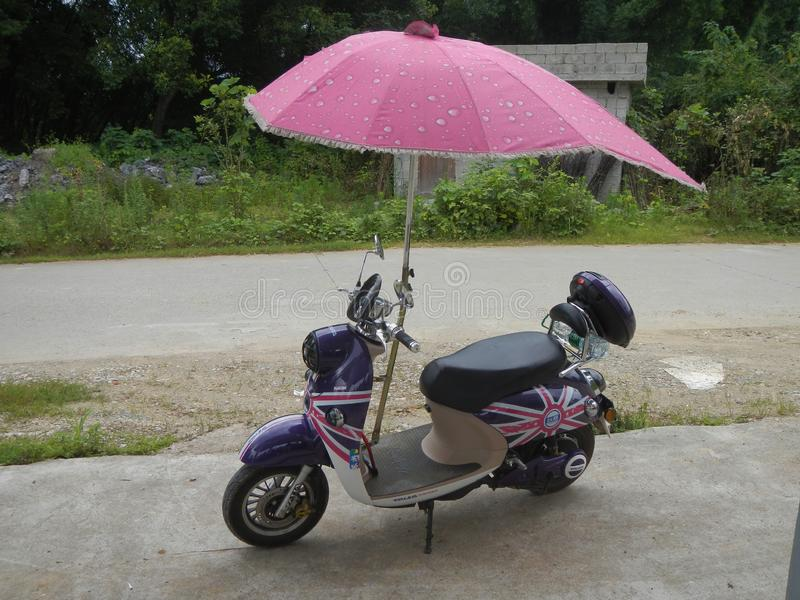 Moto sparkcykel med paraplyet arkivfoton