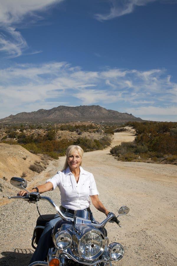 Moto supérieure d'équitation de femme sur la route de désert photos stock