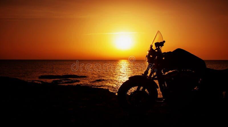 Moto sur le coucher du soleil image stock