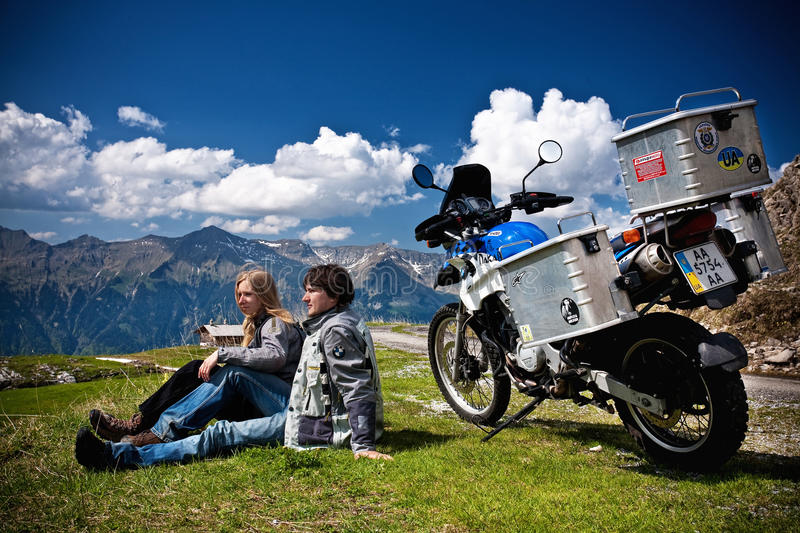 Moto travellers with motocycle in Switzerland Alps. Moto travellers with BMW motocycle in Switzerland and panorana of Alps on a background stock photos