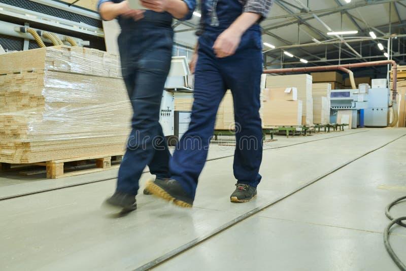 Moto vago degli uomini della fabbrica in camici fotografia stock libera da diritti