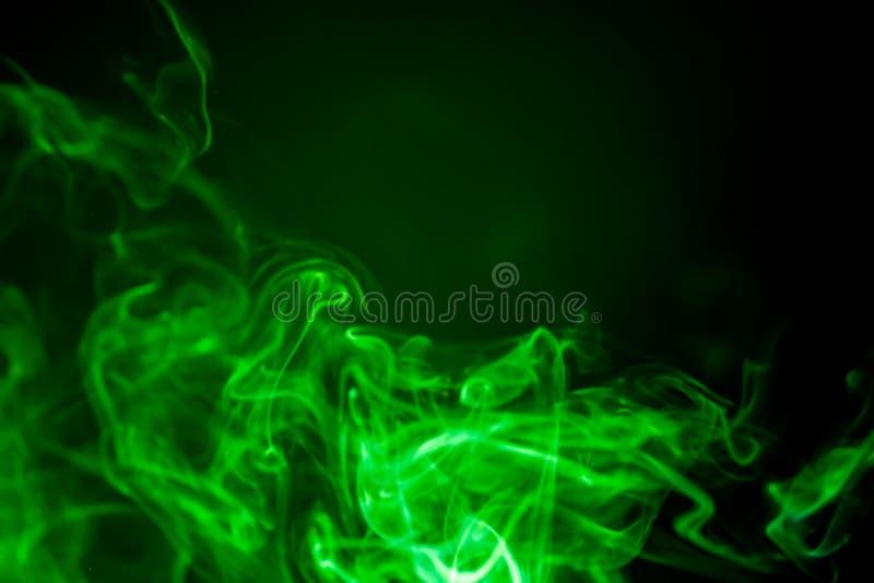 Moto verde del fumo su fondo nero immagine stock