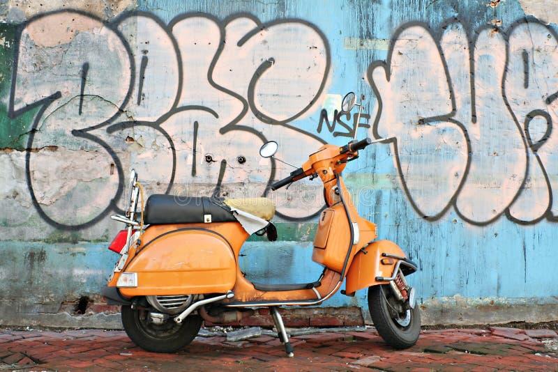 Moto vieja delante de la pared de la pintada foto de archivo libre de regalías