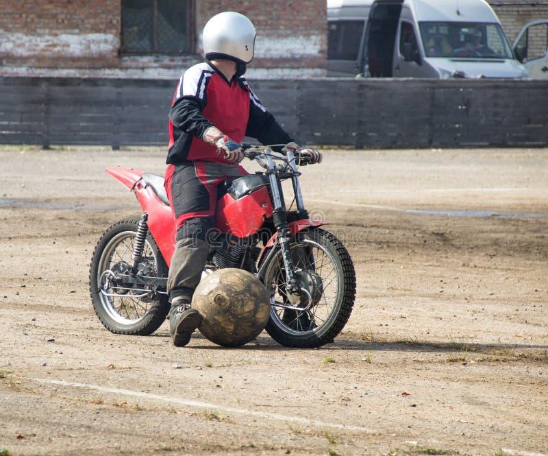 Motoball man rider en motorcykel och kör en boll med honom, närbilden, boll arkivfoton