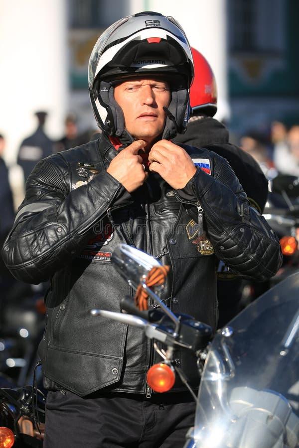 Motobiker abbottona un casco un giorno soleggiato immagini stock libere da diritti