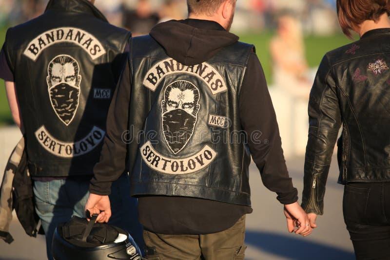Motobikers in leer bekleedt met emblemen van een motorfietsclub BANDANAS SERTOLOVO op een zonnige avond achtermenings dichte omho stock foto's