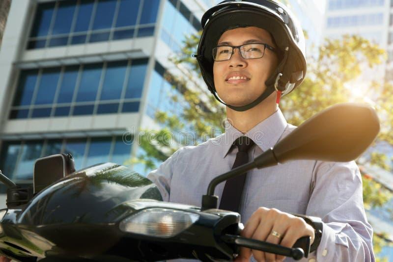 Motocicleta china de Commuter With Scooter del hombre de negocios en la mañana imagen de archivo