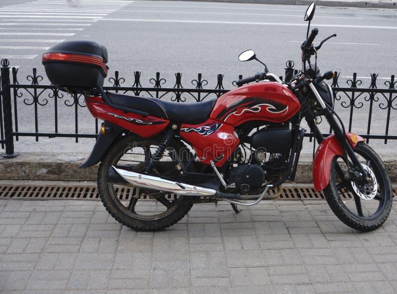 Motocicleta com um matiz vermelho e um fundo fresco foto de stock