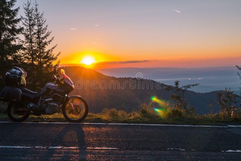 Motocicleta da aventura, velomotor turístico da silhueta os picos de montanha nas cores escuras do por do sol Copie o espaço Conc fotografia de stock royalty free