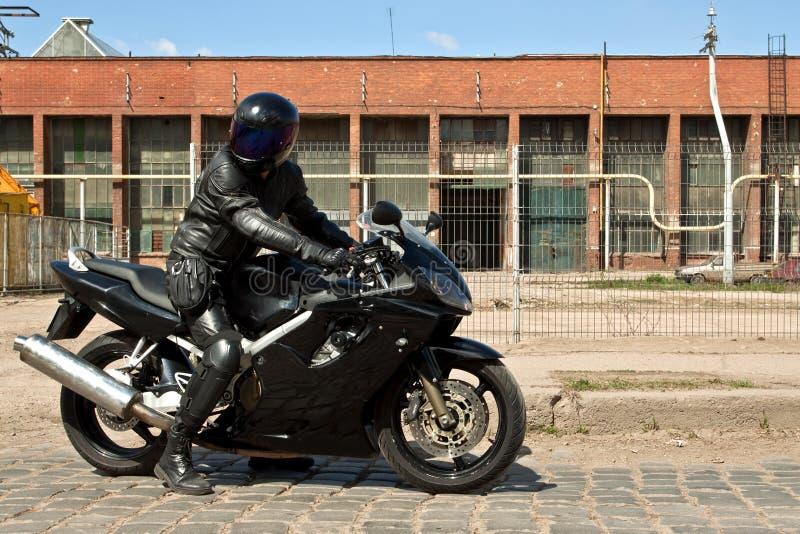 Motocicleta da equitação do motociclista na fábrica velha foto de stock royalty free