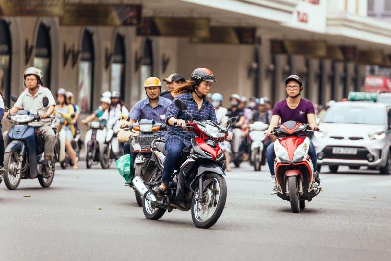 Motocicleta da equitação da mulher na estrada quando luz verde em Hanoi, Vietname imagem de stock