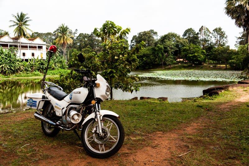 Motocicleta da polícia do turista com o lago em Angkor Wat, Camboja imagem de stock