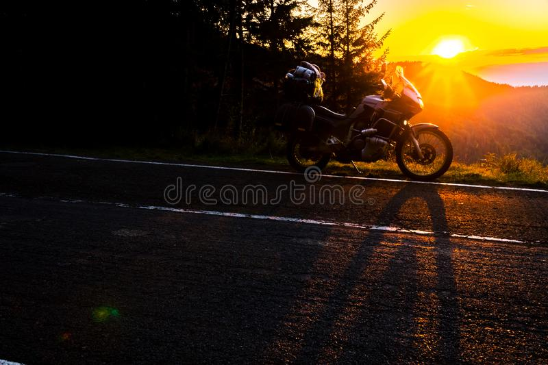 Motocicleta de la aventura, moto turística de la silueta los picos de montaña en los colores oscuros de la puesta del sol Copie e fotografía de archivo