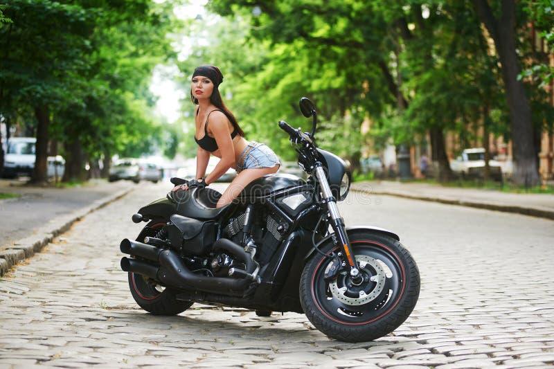 Motocicleta de la muchacha del motorista en la ciudad imágenes de archivo libres de regalías