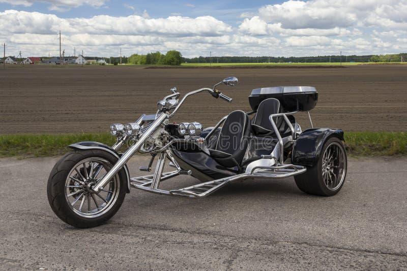 A motocicleta de três rodas está no parque de estacionamento perto do campo fotos de stock