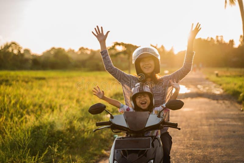 Motocicleta del montar a caballo de la madre con la hija fotos de archivo libres de regalías