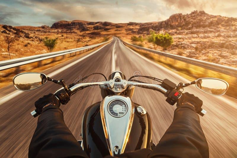 Motocicleta del montar a caballo del conductor en la carretera de asfalto