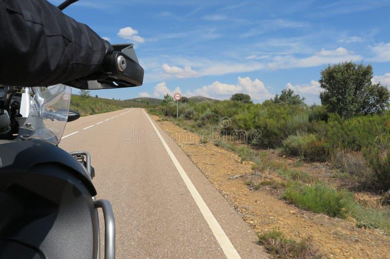 Motocicleta del montar a caballo del conductor en una carretera de asfalto imagen de archivo