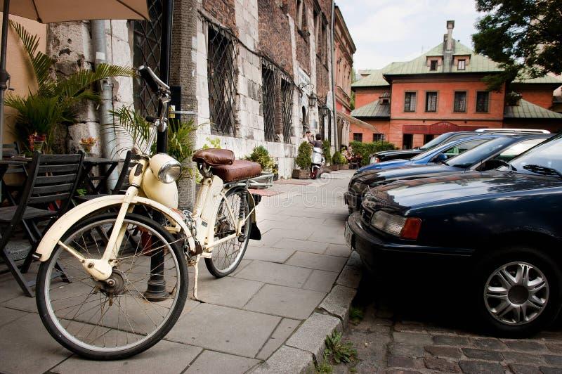 Motocicleta del vintage encadenada a posts de la lámpara fotografía de archivo