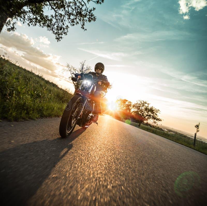Motocicleta do sportster da equitação do homem durante o por do sol fotos de stock