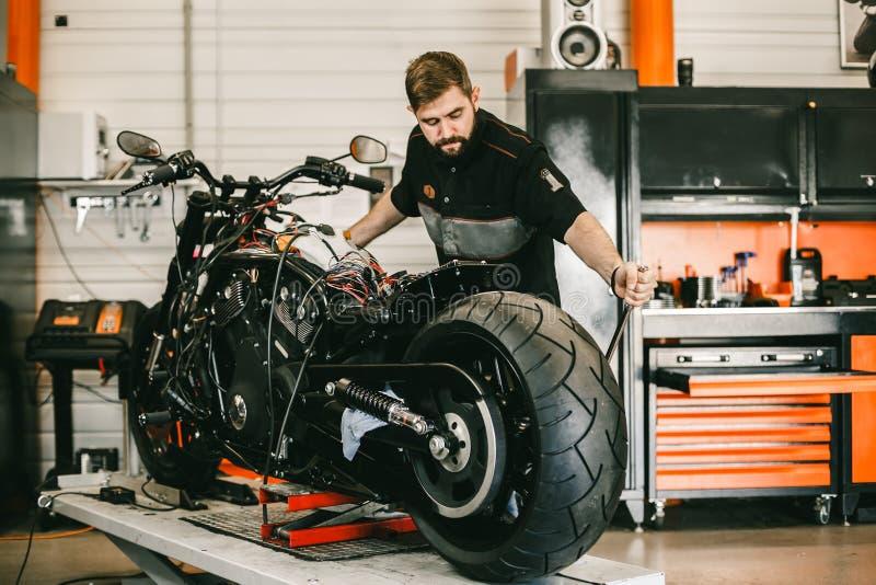 A motocicleta em mudança do Mechanician roda dentro a oficina de reparações da bicicleta imagens de stock royalty free