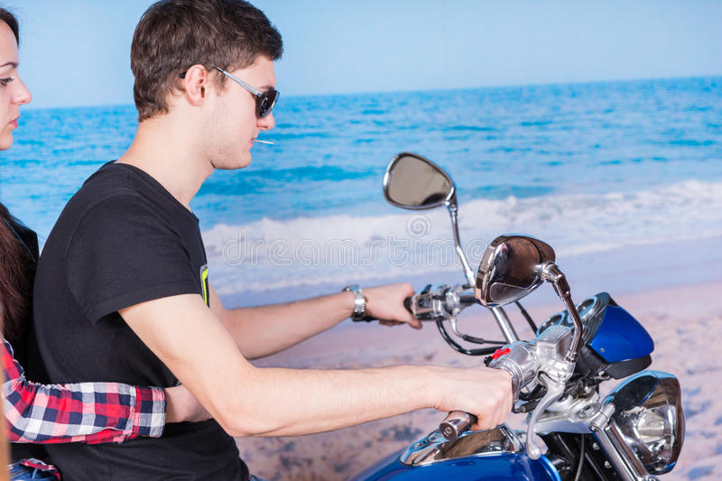 Motocicleta nova da equitação dos pares na praia foto de stock royalty free