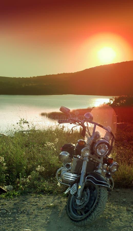 Motocicleta perto do lago na luz do por do sol fotografia de stock royalty free
