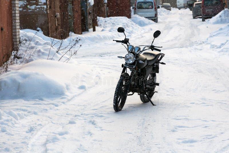 A motocicleta preta está em uma estrada nevado fotografia de stock