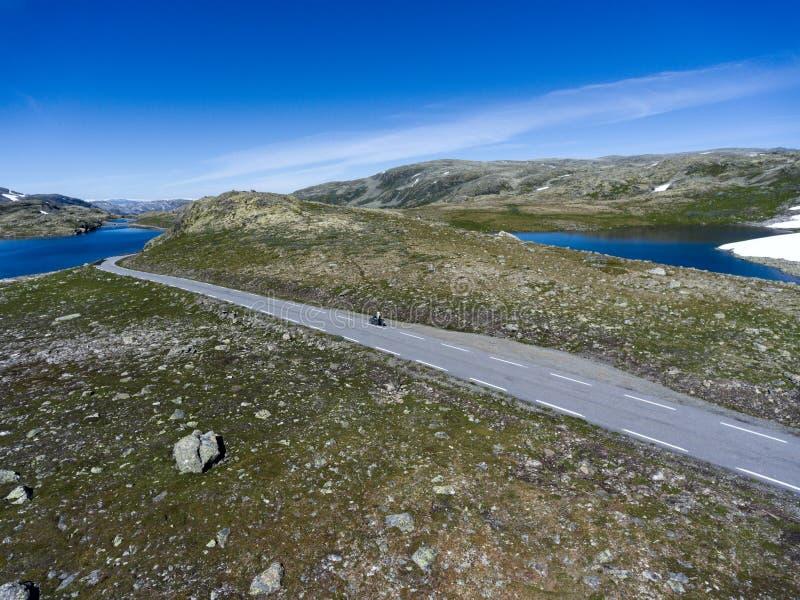 Motocicleta que conduce en la carretera de asfalto en montañas noruegas El camino Aurlandsvegen de la nieve está en Aurland, Noru imagen de archivo libre de regalías