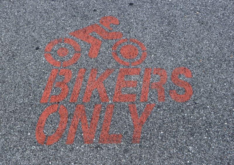 Motocicleta que estaciona somente o sinal, pintado no vermelho no asfalto com a silhueta de um motociclista do moto da equitação imagem de stock